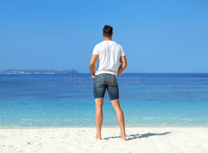 Hombre hermoso, muscular que se relaja en una playa tropical imagen de archivo