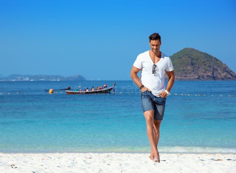 Hombre hermoso, muscular que se relaja en una playa tropical imágenes de archivo libres de regalías
