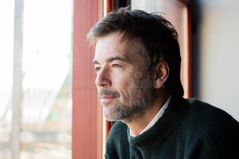 Hombre hermoso perdido en pensamiento Él ` s serio En la ventana imagen de archivo