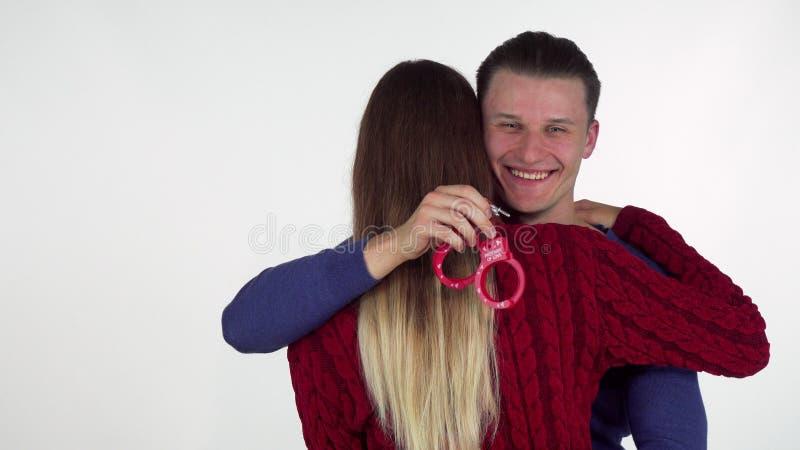 Hombre hermoso que abraza a su novia, sosteniendo las esposas del juguete del sexo detrás de su parte posterior imagenes de archivo