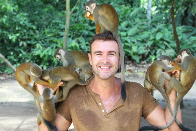 Hombre hermoso que alimenta los monos fotografía de archivo libre de regalías
