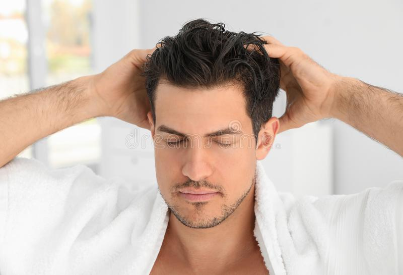 Hombre hermoso que aplica el acondicionador de pelo imágenes de archivo libres de regalías