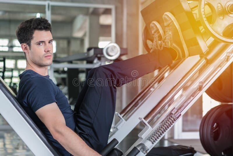 Hombre hermoso que baja las piernas del entrenamiento del peso en la máquina de la prensa de la pierna y que se resuelve en el gi fotografía de archivo