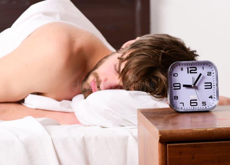 Hombre hermoso que bosteza y que estira sus brazos para arriba Imagen que muestra al hombre joven que estira en cama Divertido ac imagenes de archivo