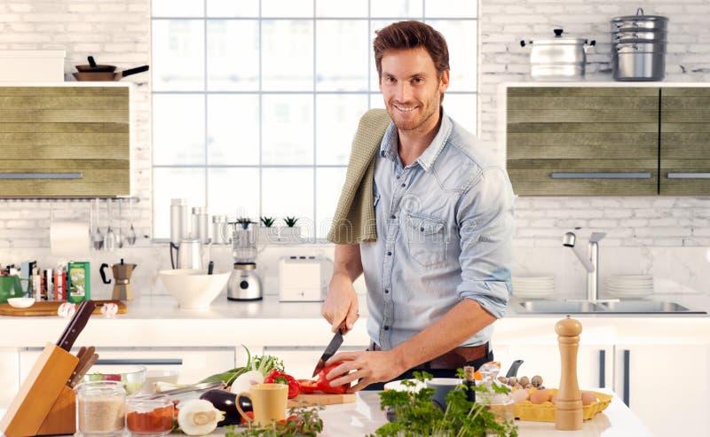Hombre hermoso que cocina en cocina en casa imagenes de archivo