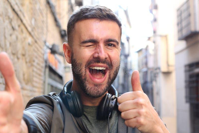 Hombre hermoso que coge un selfie y un donante pulgares y un guiño al aire libre fotos de archivo