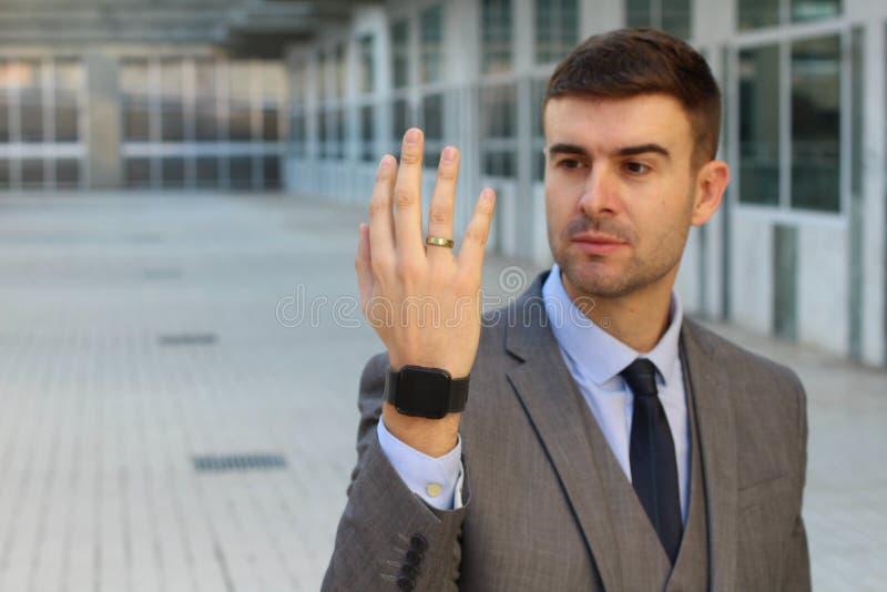 Hombre hermoso que comtempla su anillo de bodas foto de archivo libre de regalías