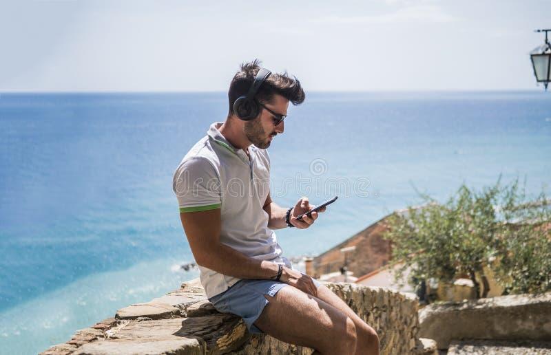Hombre hermoso que escucha la m?sica en los auriculares al aire libre imagenes de archivo