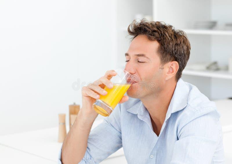 Hombre hermoso que goza de su zumo de naranja imágenes de archivo libres de regalías