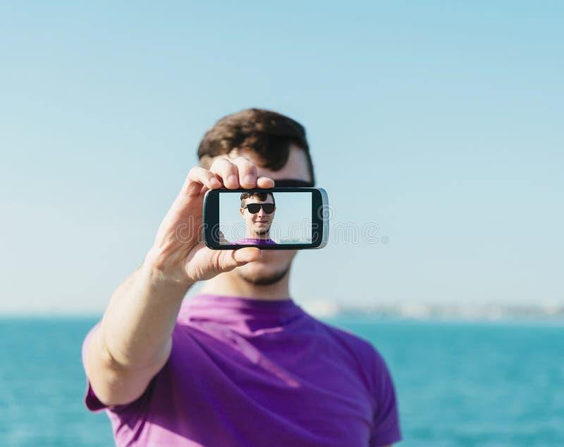 Hombre hermoso que hace un autorretrato con smartphone imágenes de archivo libres de regalías