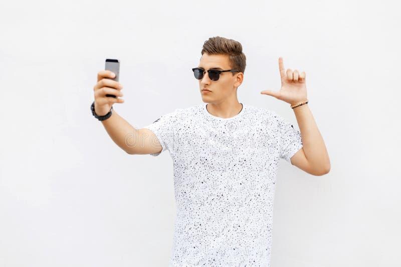 Hombre hermoso que juega a un juego en el smartphone El individuo hace el selfie fotos de archivo libres de regalías