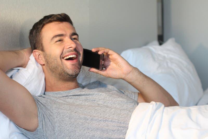 Hombre hermoso que llama por el teléfono en cama imagen de archivo
