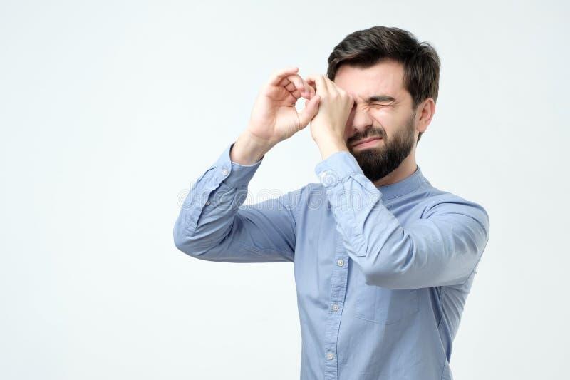 Hombre hermoso que lleva a cabo sus manos en sus ojos como si mire a través de los vidrios de espía imagenes de archivo