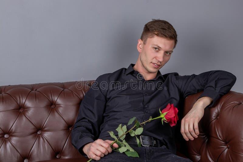 Hombre hermoso que lleva la sentada negra de la camisa en el sofá de cuero que sostiene una rosa y que consigue la fecha románt foto de archivo