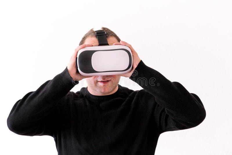 Hombre hermoso que lleva y que juega realidad virtual en fondo blanco aislado Acción del muchacho en casco de la realidad virtual foto de archivo libre de regalías
