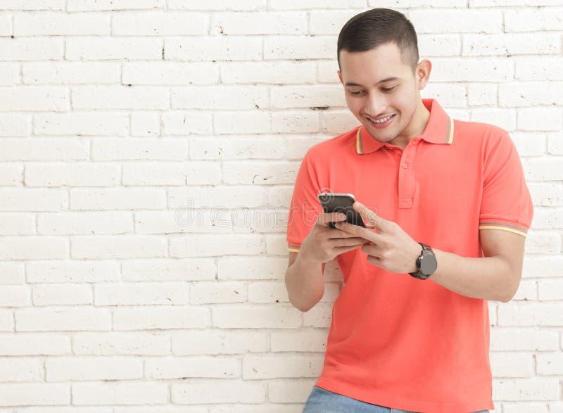 Hombre hermoso que manda un SMS en el móvil foto de archivo libre de regalías