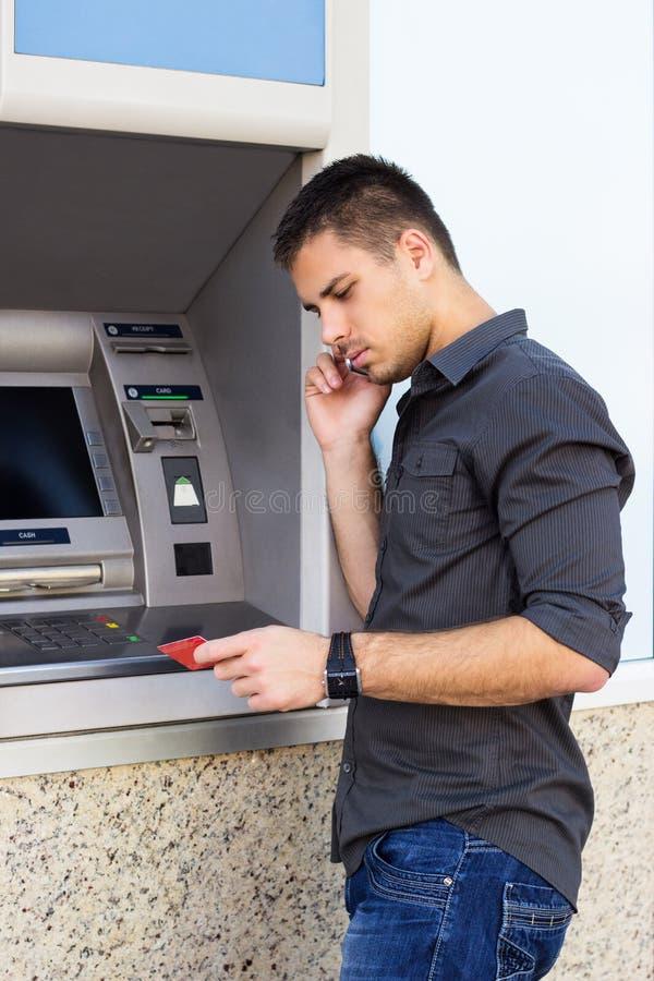 Hombre hermoso que mira una tarjeta de crédito imagen de archivo libre de regalías