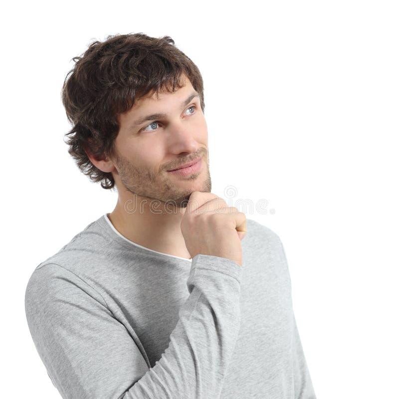 Hombre hermoso que piensa y que mira arriba con una mano en la barbilla imágenes de archivo libres de regalías