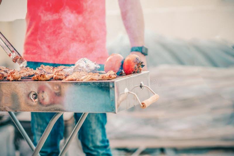 Hombre hermoso que prepara la barbacoa para los amigos Mano del hombre joven que asa a la parrilla alguna carne y verdura foto de archivo