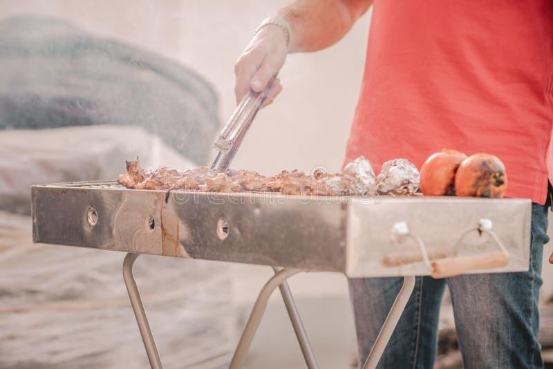Hombre hermoso que prepara la barbacoa para los amigos Mano del hombre joven que asa a la parrilla alguna carne y verdura imagenes de archivo