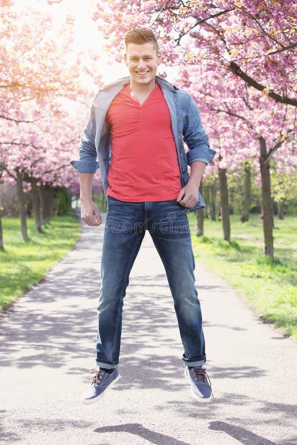 Hombre hermoso que salta al aire libre al lado de la flor de cerezo imagen de archivo