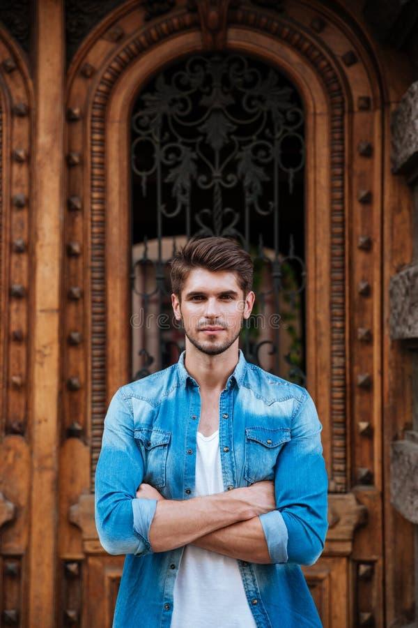Hombre hermoso que se coloca delante de la puerta de madera hermosa fotos de archivo libres de regalías