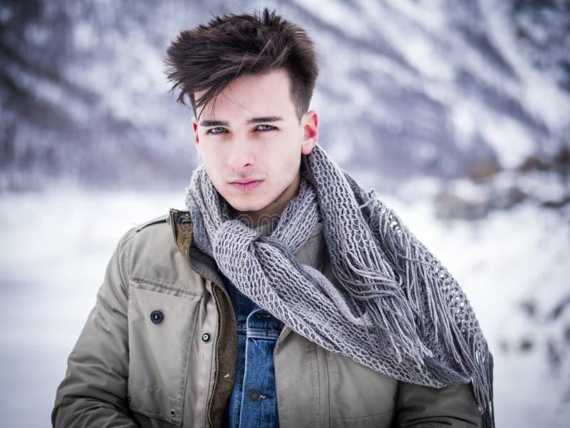 Hombre hermoso que se coloca en nieve foto de archivo