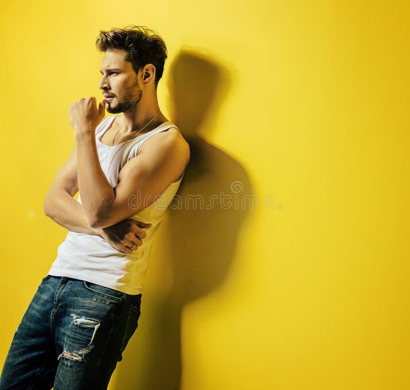 Hombre hermoso que se inclina en la pared brillante, amarilla imagen de archivo