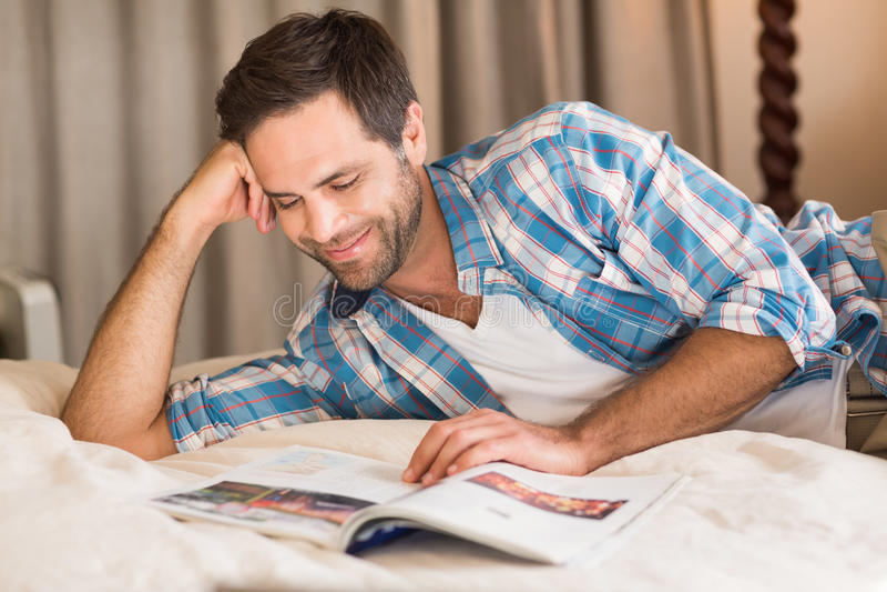 Hombre hermoso que se relaja en su revista de la lectura de la cama foto de archivo