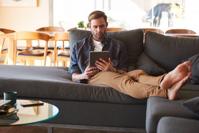 Hombre hermoso que se sienta con los pies en el sofá que sostiene la tableta electrónica imagen de archivo