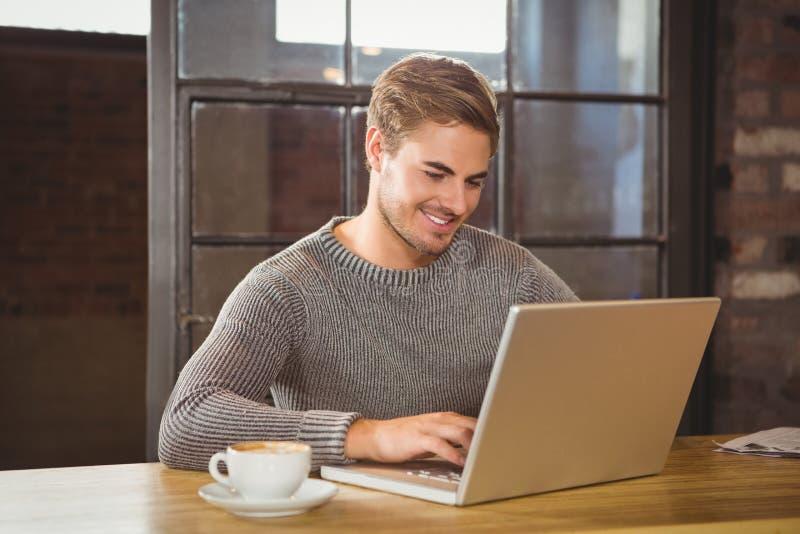 Hombre hermoso que sonríe y que mecanografía en el ordenador portátil fotografía de archivo