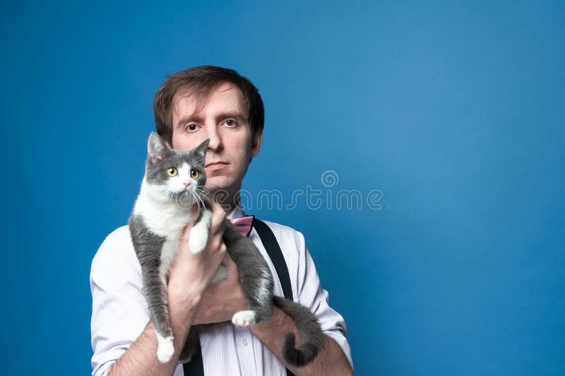 Hombre hermoso que sostiene el gato gris y blanco lindo y que mira la cámara delante del fondo azul fotos de archivo