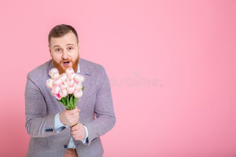Hombre hermoso que sostiene el ramo de tulipanes imagenes de archivo