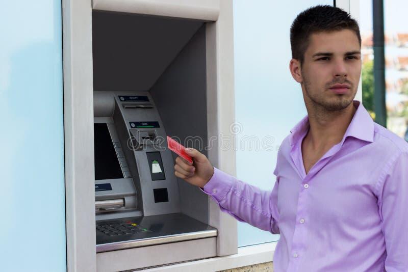 Hombre hermoso que sostiene una tarjeta de crédito imagen de archivo