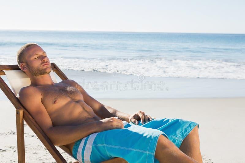 Hombre hermoso que tiene una siesta mientras que toma el sol en su silla de cubierta fotos de archivo libres de regalías