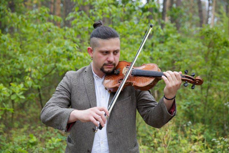 Hombre hermoso que toca el violín en fondo de la naturaleza imagen de archivo libre de regalías