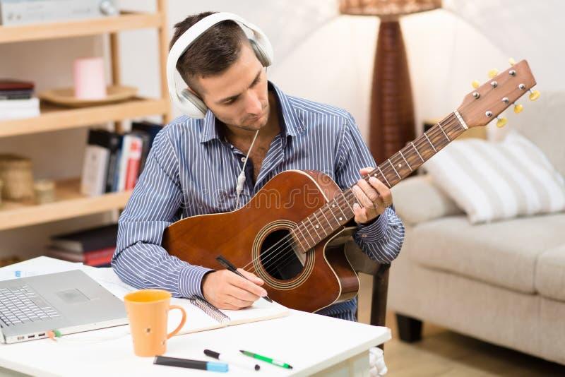 Hombre hermoso que toca la guitarra en casa fotografía de archivo libre de regalías