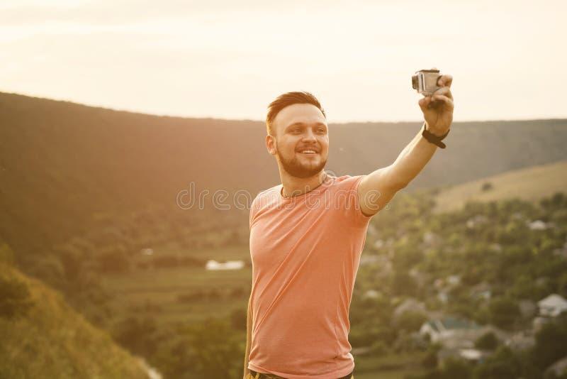 Hombre hermoso que toma a imágenes de él uno mismo con la cámara de la acción imágenes de archivo libres de regalías