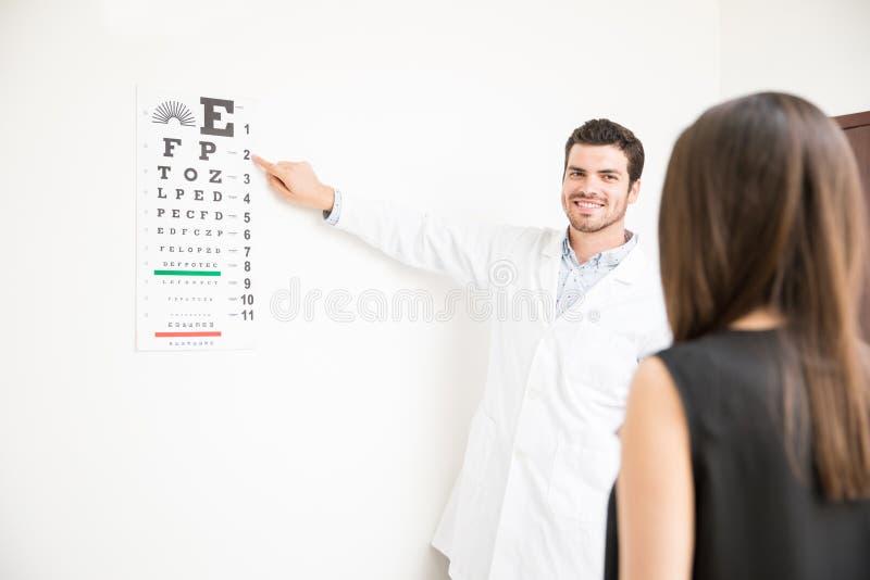 Hombre hermoso que toma la prueba del ojo de la carta del alfabeto para el paciente de la mujer imagen de archivo