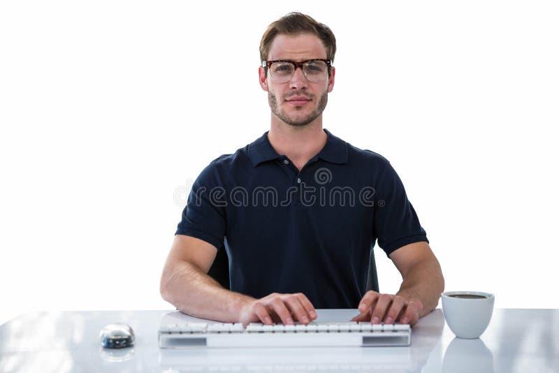 Hombre hermoso que usa el ordenador mientras que bebe el café imagenes de archivo