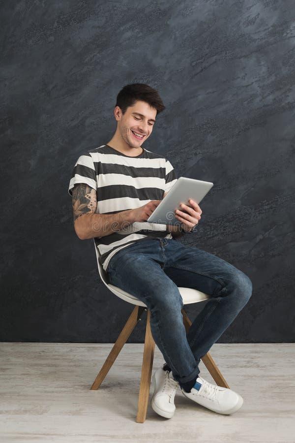 Hombre hermoso que usa la tableta digital en estudio fotografía de archivo