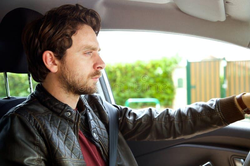 Hombre hermoso serio con la barba y el pelo largo que conducen el coche fotografía de archivo