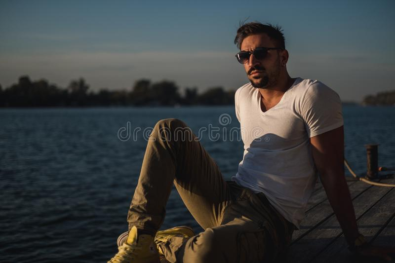 Hombre hermoso serio que piensa por el río foto de archivo