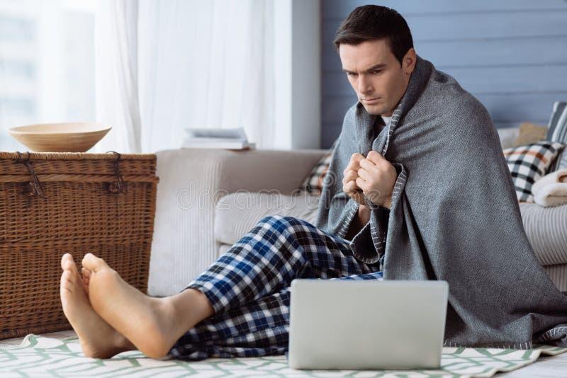 Hombre hermoso serio que se sienta en el piso imagen de archivo libre de regalías