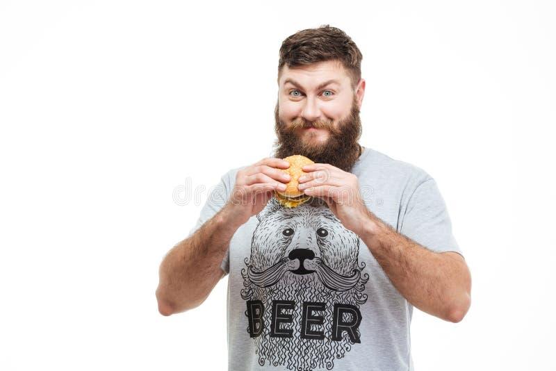 Hombre hermoso sonriente con la barba que coloca y que sostiene la hamburguesa imagenes de archivo