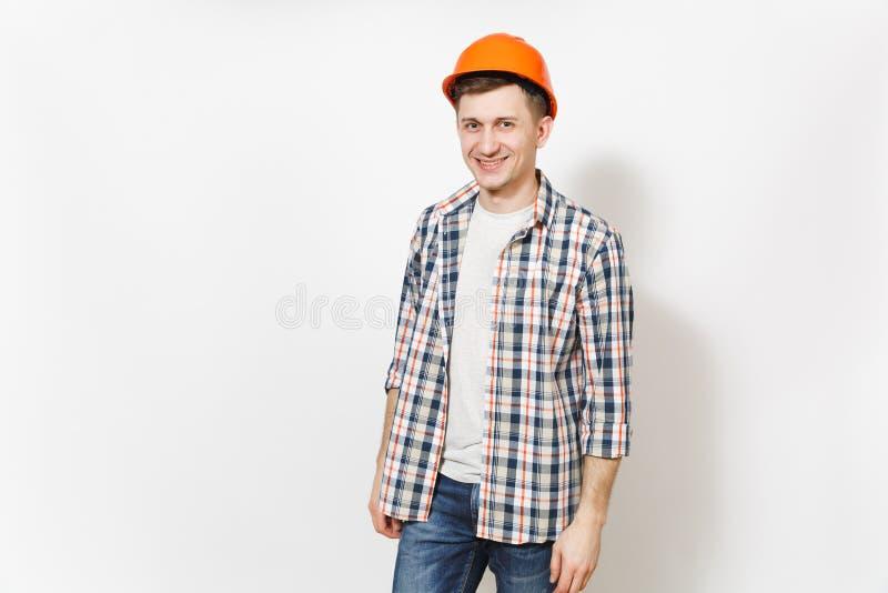 Hombre hermoso sonriente joven en ropa casual y el casco anaranjado de la construcción protectora aislado en el fondo blanco fotografía de archivo libre de regalías