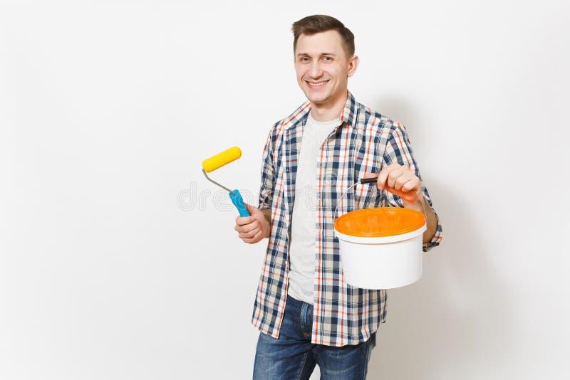 Hombre hermoso sonriente joven que sostiene el rodillo de pintura para la pintura de pared y el cubo vacío de la pintura con el e foto de archivo
