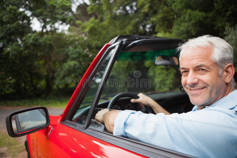 Hombre hermoso sonriente que conduce el cabriolé rojo fotografía de archivo