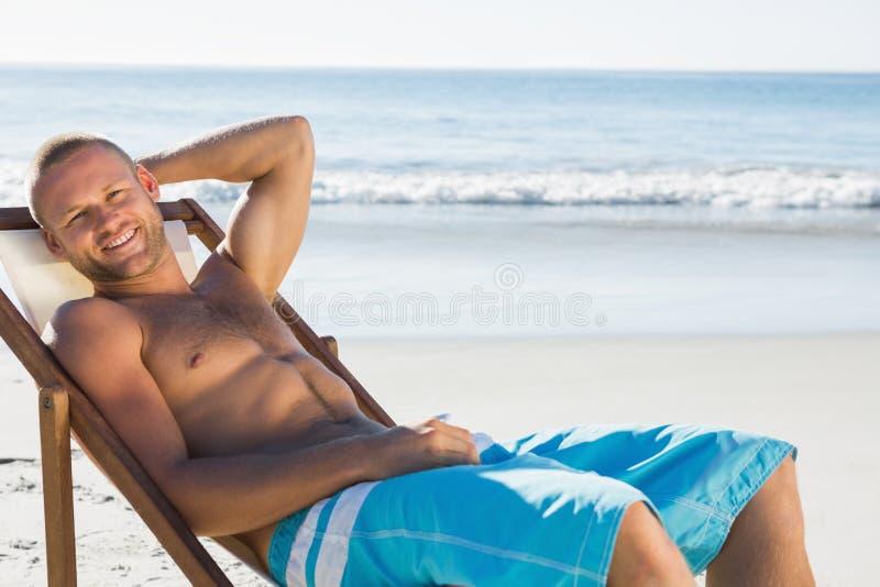 Hombre hermoso sonriente que toma el sol en su silla de cubierta fotografía de archivo libre de regalías