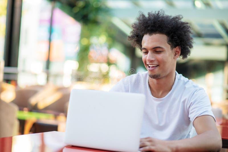 Hombre hermoso victorioso que mira su ordenador port?til mientras que se sienta en sala de estar brillante imagenes de archivo